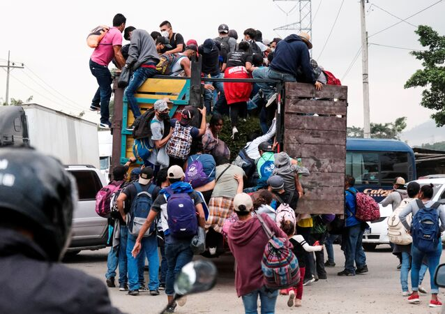 Hondurans climb onto the back of a truck for a ride in a new caravan of migrants, set to head to the United States, in Cofradia, Honduras January 15, 2021.