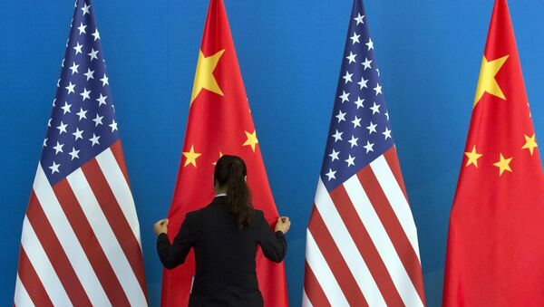 A Chinese woman adjusts the Chinese national flag near U.S. national flags before a Strategic Dialogue expanded meeting that's part of the U.S.-China Strategic and Economic Dialogue at the Diaoyutai State Guesthouse in Beijing, Thursday, July 10, 2014 - Sputnik International
