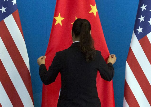 A Chinese woman adjusts the Chinese national flag near U.S. national flags before a Strategic Dialogue expanded meeting that's part of the U.S.-China Strategic and Economic Dialogue at the Diaoyutai State Guesthouse in Beijing, Thursday, July 10, 2014