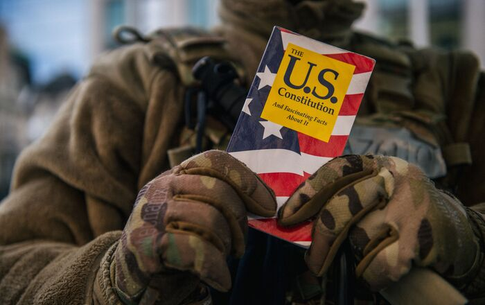 WASHINGTON, DC - JANUARY: 17 National Guard Master Sergeant George Roachs holds up a pamphlet of the U.S. Constitution on January 17, 2021 in Washington, DC.