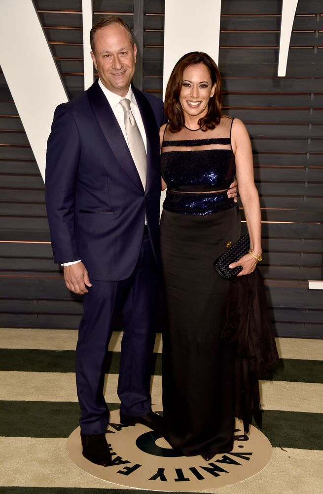 Attorney Douglas Emhoff (L) and California Attorney General Kamala Harris attend the 2015 Vanity Fair Oscar Party hosted by Graydon Carter at the Wallis Annenberg Centre for the Performing Arts on 22 February 2015 in Beverly Hills, California. Harris is donning a floor-length bodycon midnight blue and black gown, with a see-through waistline and upper part.