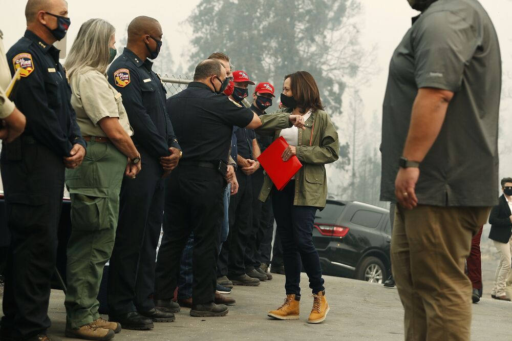 Democratic vice presidential candidate Sen. Kamala Harris, D-Calif., bumps elbows with first responders as she was briefed on the Creek Fire at Pine Ridge Elementary, Tuesday, 15 September 2020 in Auberry, Calif. Harris is seen wearing a casual jacket-jeans ensemble, complete with classic brown Timberland boots.
