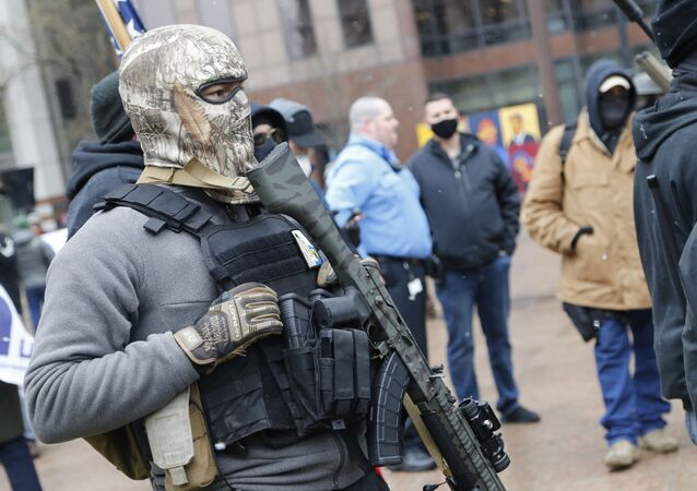 An armed protestor stands outside the Ohio Statehouse Sunday, Jan. 17, 2021, in Columbus, Ohio