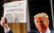 President Donald Trump holds up a copy of USA Today's front page showing news of his acquittal in his first Senate impeachment trial.