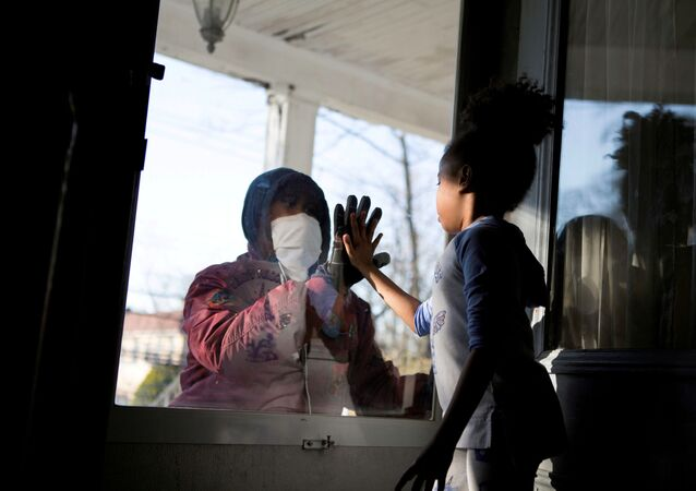 Hashim, an essential worker in the healthcare industry, greets his daughter through the closed door, maintaining social distance from his family as he works with the coronavirus disease (COVID-19) outbreak in New Rochelle, New York, US, 11 April 2020.