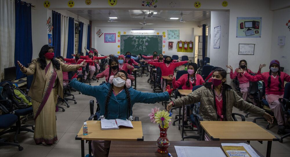 School pupils make hugging signs outside class as schools reopen after being closed for months because of the coronavirus pandemic in New Delhi, India, Monday, 18 January 2021.