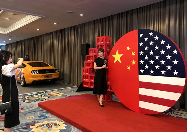 Two women take a photo at a display representing the US and Chinese flags at a reception marking 40 years of diplomatic relations between the US and China, at a hotel in Beijing on June 21, 2019