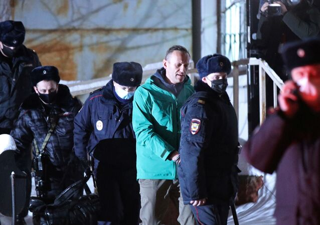 Russian opposition leader Alexei Navalny is escorted by police officers after a court hearing, in Khimki outside Moscow, Russia January 18, 2021.