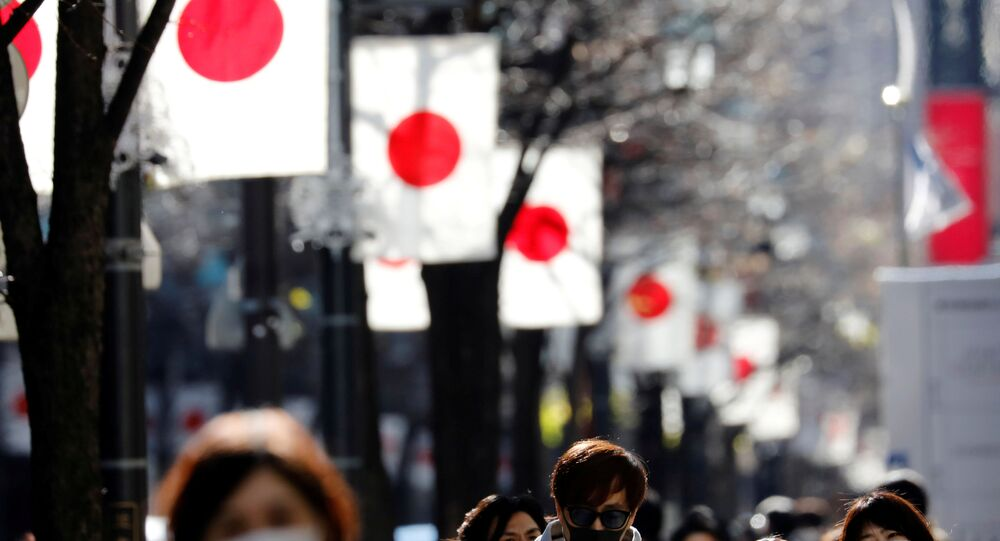 Pedestrians wearing protective masks, amid the coronavirus disease (COVID-19) outbreak, make their way at Ginza shopping district which closed to cars on Sunday in Tokyo, Japan, January 10, 2021. REUTERS/Kim Kyung-Hoon