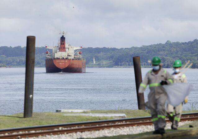A cargo ship navigates through Panama Canal waters near Gamboa