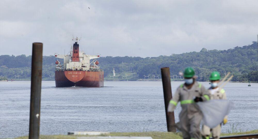 A cargo ship navigates through Panama Canal waters near Gamboa