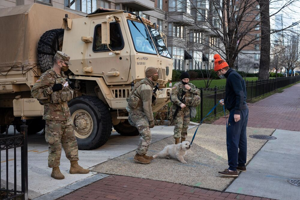 National Guard troops talk to a local resident ahead of the inauguration of President-elect Joe Biden in Washington, DC, the United States.