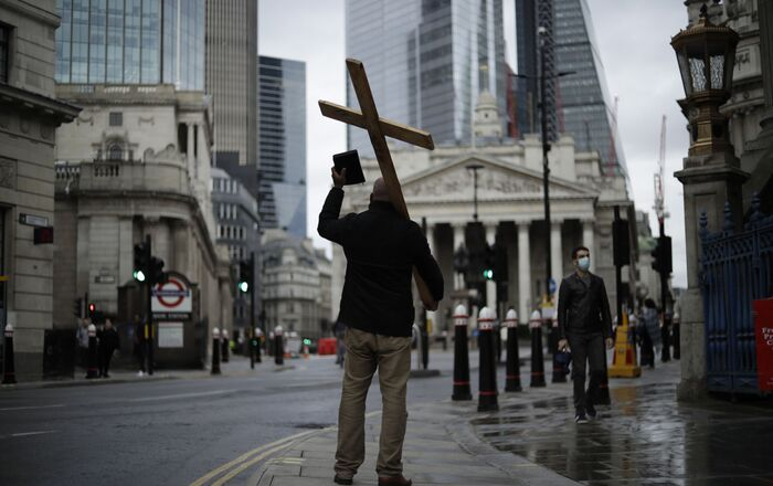 A man holding a cross and a Bible preaches about Christianity backdropped by the Royal Exchange, back center, and the Bank of England, at left, during England's second coronavirus lockdown in the City of London financial district of London, Wednesday, Nov. 18, 2020