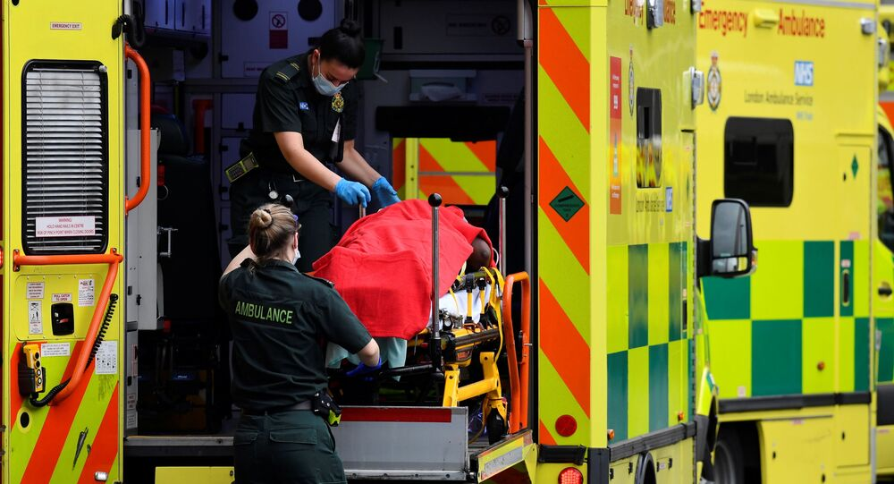 Medical workers bring a patient out of an ambulance, amid the coronavirus disease (COVID-19) pandemic, outside Royal London Hospital, in London, Britain, January 15, 2021