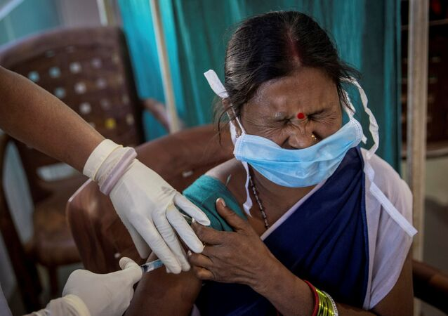 A healthcare worker winces as she receives a dose of COVISHIELD, a COVID-19 vaccine manufactured by Serum Institute of India, during one of the world's largest COVID-19 vaccination campaigns at Mathalput Community Health Centre in Koraput district of the eastern state of Odisha, India, 16 January 2021.