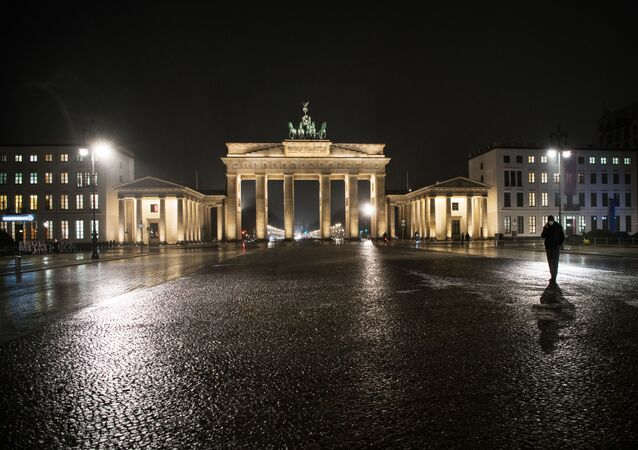 A man with a protective face mask walks on empty Pariser Platz in front of Brandenburger Gate on January 19, 2021 in Berlin amid the novel coronavirus COVID-19 pandemic.