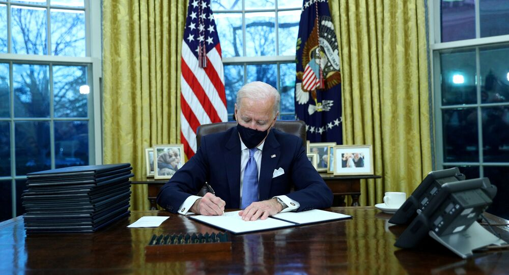 U.S. President Joe Biden signs executive orders in the Oval Office of the White House in Washington, after his inauguration as the 46th President of the United States, U.S., January 20, 2021.