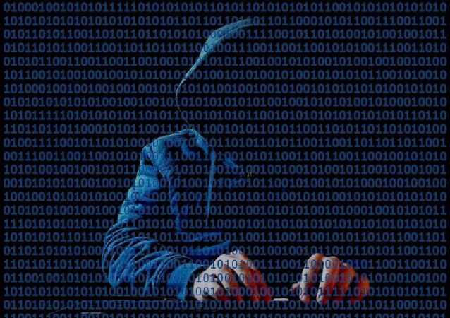 Hooded hacker at keyboard with binary code in front