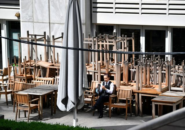 A person sits on a chair outside a closed pub in Canary Wharf, following the outbreak of the coronavirus disease (COVID-19), London, Britain, May 27, 2020