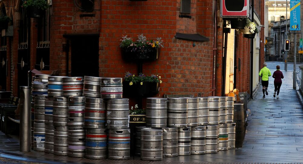 People run past a pile of empty beer barrels outside a closed pub amid the COVID-19 pandemic in Belfast, Northern Ireland January 2, 2021