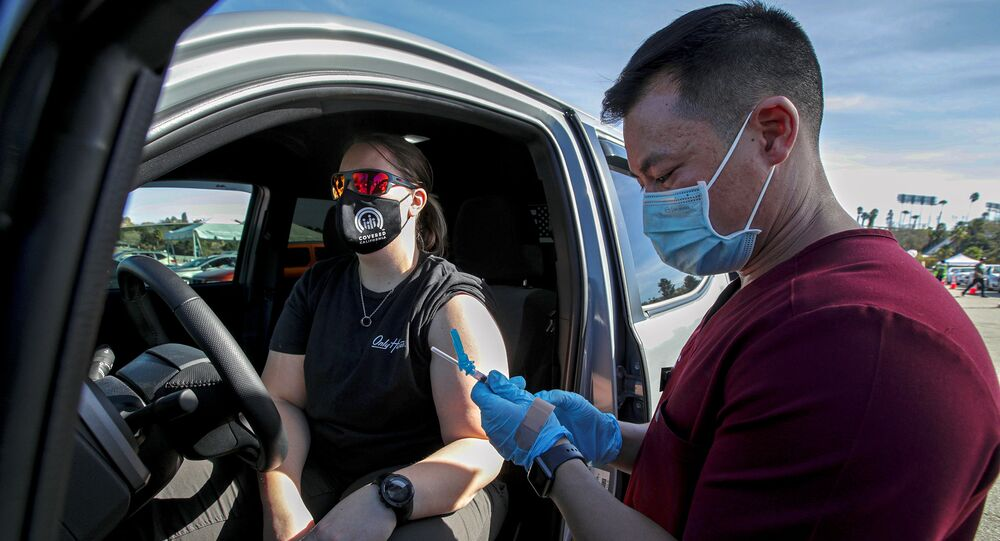 Dr. Richard Dang, assistant professor USC School of Pharmacy administers COVID-19 vaccine to Ashley Van Dyke (L) as mass-vaccination of healthcare workers takes place at Dodger Stadium in Los Angeles, California, U.S., January 15, 2021