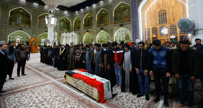 Mourners gather near the coffin of a man, who was killed in a twin suicide bombing attack in a central Baghdad market, during a funeral in Najaf, Iraq, January 21, 2021.