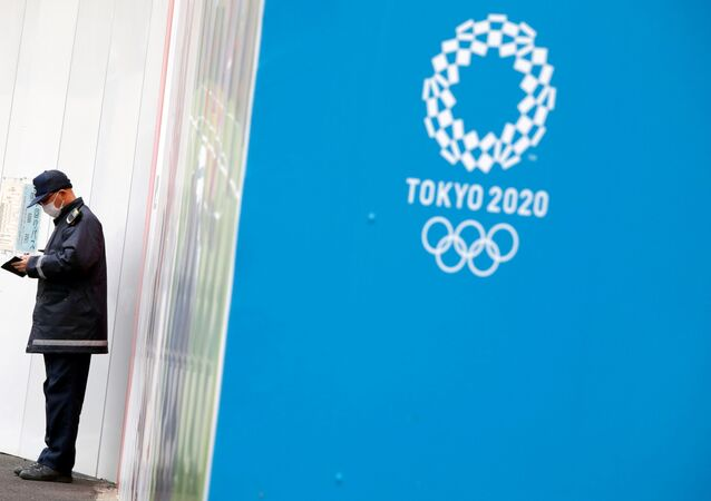 A security officer stands next to the Tokyo 2020 Olympic Games logo, amid the coronavirus disease (COVID-19) outbreak in Tokyo, Japan December 24, 2020.