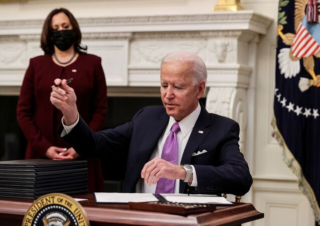 U.S. President Joe Biden signs an executive order as part of his administration's plans to fight the coronavirus disease (COVID-19) pandemic during a COVID-19 response event as Vice President Kamala Harris stands by at the White House in Washington, U.S., January 21, 2021.