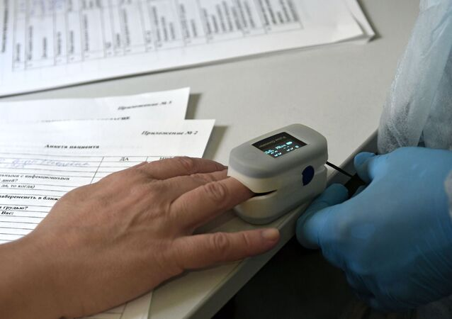 A health worker measures oxygen in blood before being vaccinated against COVID-19 with the Sputnik V (GamCOVIDVac) vaccine at a mobile station in Krasnodar.