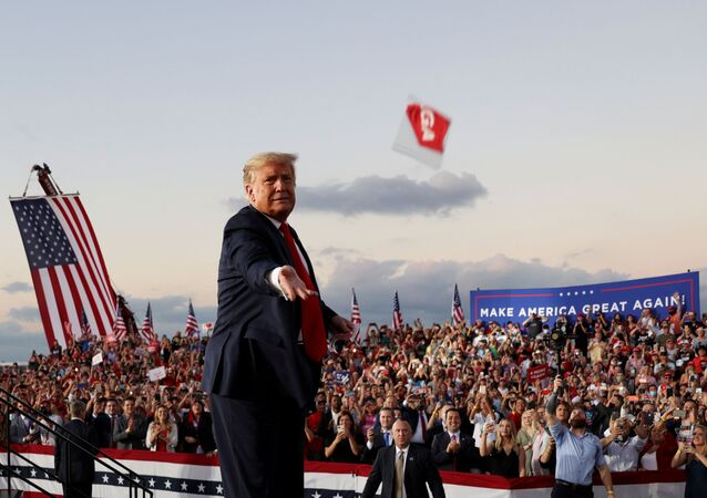 FILE PHOTO: U.S. President Donald Trump throws a face mask from the stage during a campaign rally, his first since being treated for the coronavirus disease (COVID-19), at Orlando Sanford International Airport in Sanford, Florida, U.S., October 12, 2020.