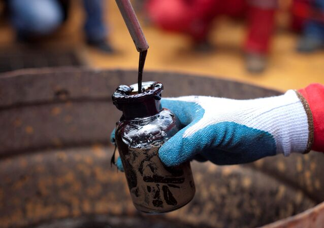 A worker collects a crude oil sample at an oil well operated by Venezuela's state oil company PDVSA in Morichal, Venezuela, 28 July 2011.