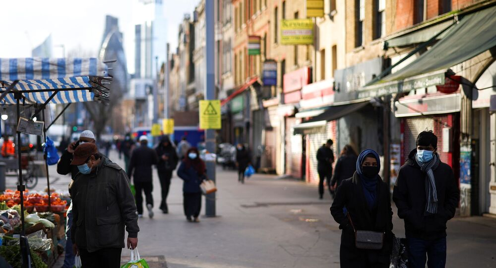 People walk past shops and market stalls, amid the coronavirus disease (COVID-19) outbreak, in east London, Britain, January 23, 2021.