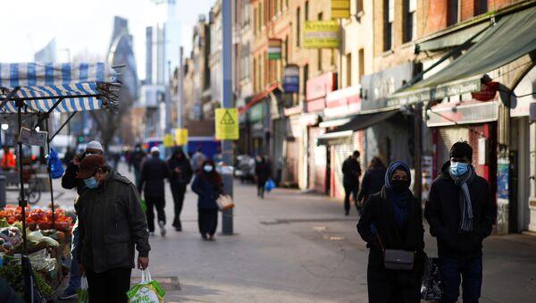 People walk past shops and market stalls, amid the coronavirus disease (COVID-19) outbreak, in east London, Britain, January 23, 2021. - Sputnik International