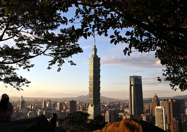 People take photos with Taiwan's landmark building Taipei 101 in the background ahead of the Chinese New Year in Taipei, Taiwan, January 20, 2021.
