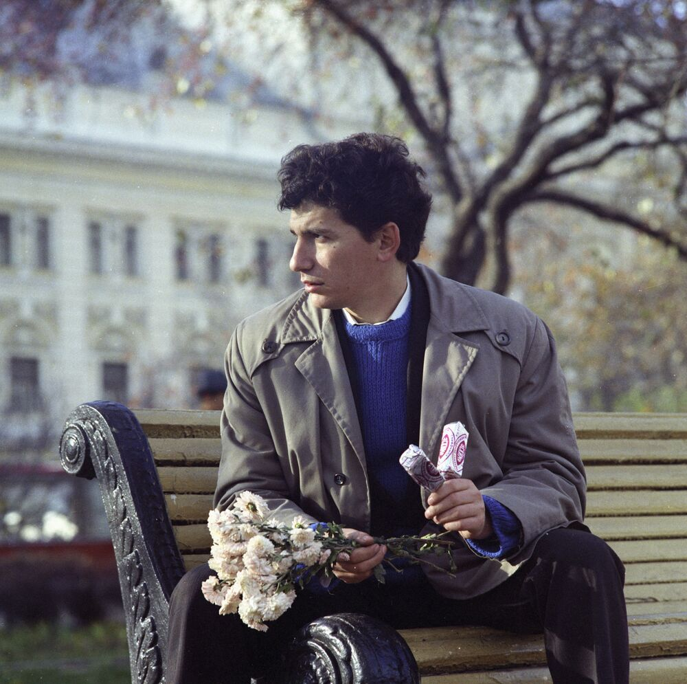 A man waits for his girlfriend, holding a bunch of flowers and two Eskimo pies. Moscow, 1973.