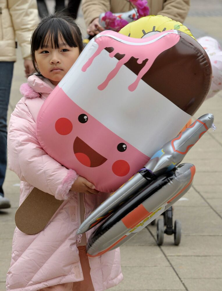 A girl walks home with a giant blow up ice cream at a Chinese New Year fair at a local park in Hong Kong on 4 February, 2008.