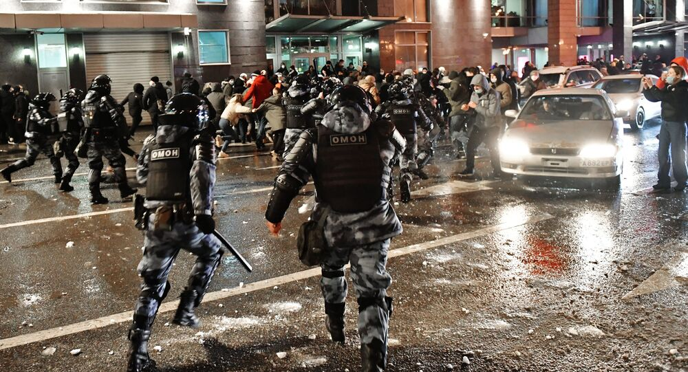 Riot police react as protesters run during an unauthorised rally in Moscow 23 January 2021