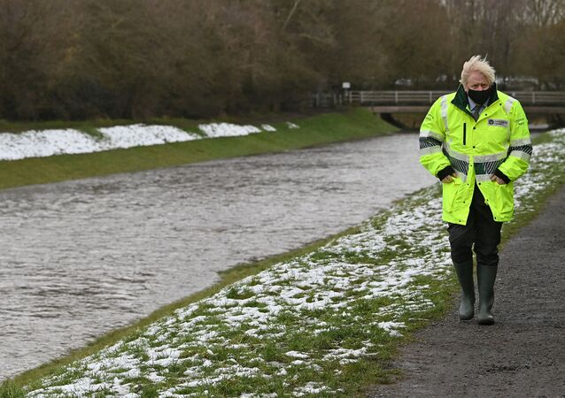 Britain's Prime Minister Boris Johnson reacts during his visit to a storm basin near the River Mersey in  Didsbury, Manchester, as Storm Christoph brings heavy rains and flooding across the country, Britain January 21, 2021