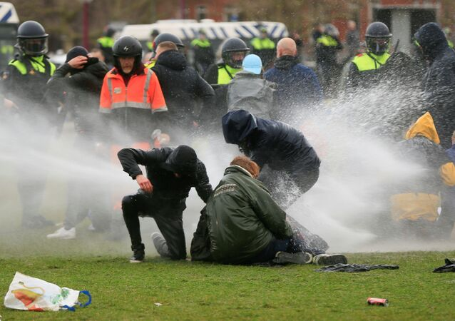 Police uses a water canon during a protest against restrictions put in place to curb the spread of the coronavirus disease (COVID-19), in Amsterdam, Netherlands January 24, 2021.