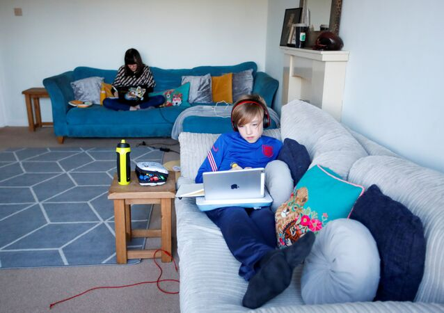 FILE PHOTO: Two home-schooled children attend their lessons at home in Milton Keynes, Britain, January 5, 2021