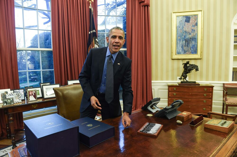 US President Barack Obama gets up after signing a compromise $1.1 trillion spending package that funds the government through September 2016 in the Oval Office at the White House in Washington, DC, on 18 December 2015.