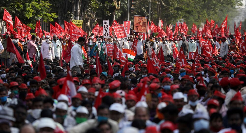 Farmers hold flags and placards during a protest against new farm laws in Mumbai, India, 25 January 2021.