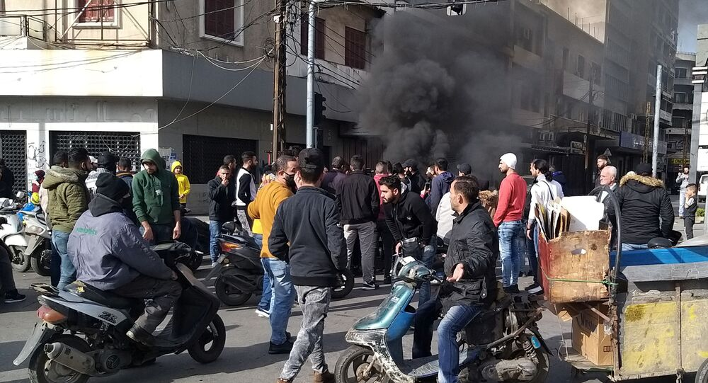 Smoke rises as demonstrators protest against the lockdown and worsening economic conditions, amid the spread of the coronavirus disease (COVID-19), in Tripoli
