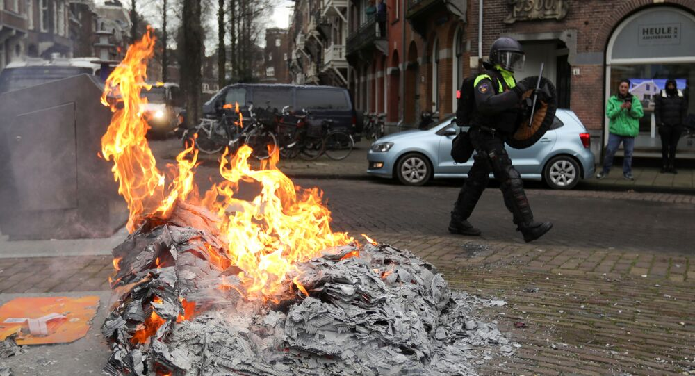 A police officer walks near a fire during a protest against restrictions put in place to curb the spread of the coronavirus disease (COVID-19), in Amsterdam, Netherlands January 24, 2021