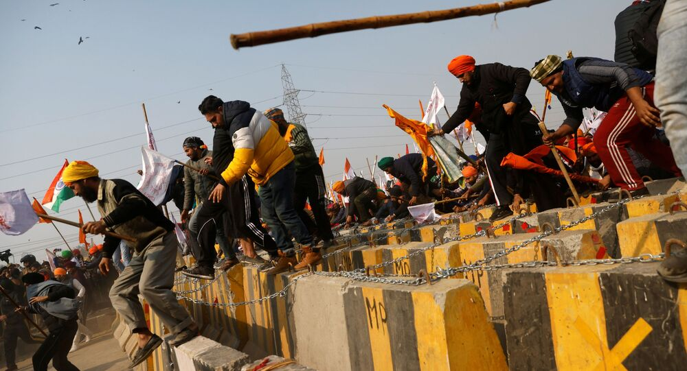 Farmers cross a barricade during a tractor rally to protest against farm laws on the occasion of India's Republic Day in Delhi, India, January 26, 2021