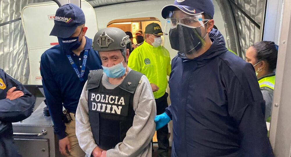 In this photo released by the Colombian Migration Press Office, ex-paramilitary commander Hernan Giraldo Serna, center, is escorted upon arrival at the El Dorado airport after being deported from the U.S. to Bogota, Colombia, Monday, Jan. 25, 2021. Giraldo, 74, was deported from the U.S. and immediately taken into custody by authorities in Colombia, where he is expected to serve time for crimes against humanity, including torture, displacement, sexual slavery and kidnapping, as well as drug trafficking