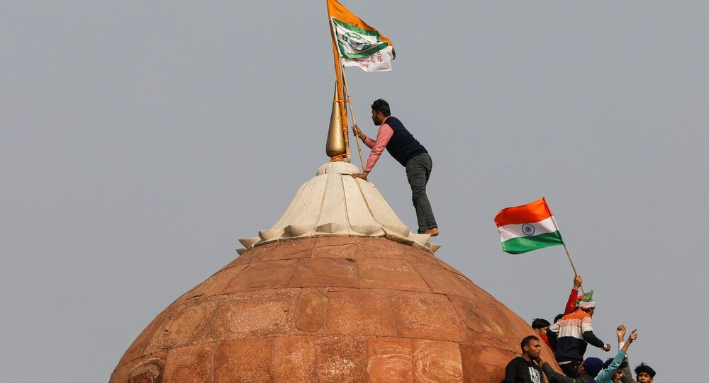 A farmer puts a flag on top of the historic Red Fort, during a protest against farm laws introduced by the government, in Delhi, India, January 26, 2021