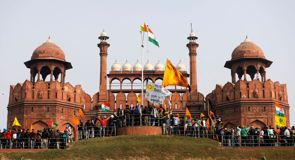 Farmers wave flags during a protest against farm laws introduced by the government, at the historic Red Fort in Delhi, India, January 26, 2021
