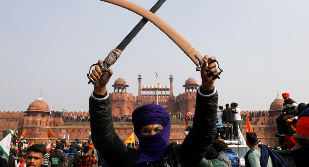 A farmer holds a sword aloft during a protest against farm laws introduced by the government, at the historic Red Fort in Delhi, India, 26 January 2021.