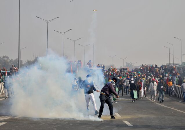 A man throws a tear gas canister back at police during a tractor rally held by farmers to protest farm laws on the occasion of India's Republic Day at Ghazipur border near Delhi